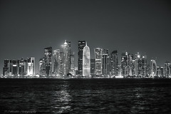 City lights (Paterdimakis) Tags: city sea sky urban bw black west reflection building tower water lines architecture night skyscraper dark bay blackwhite cityscape shape doha qatar blackwhitephotos