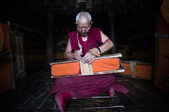 Librarian (Ravikanth K) Tags: 500px librarian thikse monastery orange books wooden plank packing rope monk old man people indoor library gompa leh ladakh lowlight maroon tradition