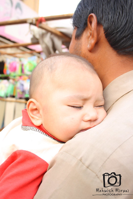 cute baby sleeping his father's shoulder