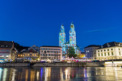 Cantons on the Grossmnster (Tambako the Jaguar) Tags: grossmnster projections light cantons limmat buildings bridge tower bluehour sky zrifscht zri fest feast zrich switzerland nikon d5