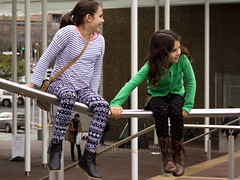 Sliding on Rails (C & R Driver-Burgess) Tags: girls sitting rail pillar green two together perched striped patterned spotted plain tights bag ponytail asian kiwi black hair indian leather boots aotea square auckland city centre