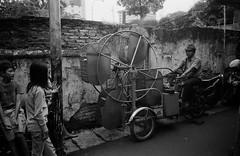 Tiny Ferris Wheel (Purple Field) Tags: contax tvs carl zeiss variosonnar 28mmf3556mmf65 fuji neopan iso400 presto bw monochrome film analog 35mm jakarta indonesia street alley walking tricycle ferris wheel                    children