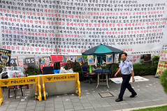 Cheating (Mondmann) Tags: seoul korea southkorea rok republicofkorea demonstration protest freespeech signs protestsigns securityguard sidewalk street asia eastasia northeastasia mondmann appleiphone5s iphone5s yongsan
