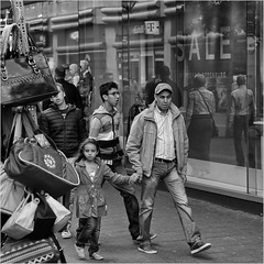 Bags for sale (John Riper) Tags: johnriper street photography straatfotografie rotterdam square bw black white zwartwit mono monochrome netherlands candid john riper canon 6d 24105 l people kid father daughter hoogstraat bags market stall shop window reflections sale peek cloppenburg peekcloppenburg cap tmobile enrico benetti