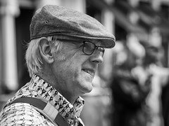 A likely lad (Nikonsnapper) Tags: olympus omd em1 zuiko 75mm bw candid portrait unposed flat cap help glasses smile