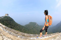 young woman backpacker on great wall in china (esl_suite_andy) Tags: hiking woman hiker chinese greatwall steep mountain peak backpack backpacker china determinted success travel outdoor sky stone rock bricks watchtowers yellow orange asian asia japanese korean female girl young 20s 2530 30s rural landscape copyspace nature trail watch looking