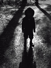 Gloom (Tammy Schild) Tags: light blackandwhite reflection silhouette 35mm puddle hoodie kid shadows child darkness mud sigma rainboots