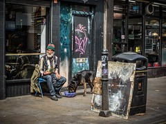Pooch and his man (sara.wendelmelhuish) Tags: street candid eastend bricklane man dog london moment pooch londonphotography shop cafe streetphotography urban reflection window door bin chair bowl dogfood feeding canine