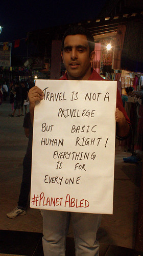 Poster Campaign: Pranav is holding a poster which reads, 'travel is not a privilege but a basic human right! Everything is for everyone'.