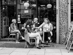 Northern Quarter #127 (Peter.Bartlett) Tags: manchester bag eyecontact women window unitedkingdom city urbanarte door lunaphoto girl candid uk m43 couple cafe niksilverefex shopfront people streetphotography doorway woman shopwindow sitting chair smoking man drink urban peterbartlett olympuspenf coffeecup noiretblanc microfourthirds monochrome menu cigarette sign blackandwhite bw men table