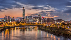 Cloudy Sunset  (Sharleen Chao) Tags: city longexposure winter sunset urban building skyline night skyscraper canon river landscape cityscape riverside taiwan clear 101  taipei nightscene bluehour taipei101    starburst afterglow 70200mm partlycloudy 101  capitalcity  riverreflection    canoneos5dmarkiii pwpartlycloudy