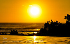 Engulfing Yellow (jaymcbridecom) Tags: ocean travel trees sunset shadow bali reflection water pool yellow clouds reflections indonesia landscape bright dusk infinity flags shade strength rough traveling too infinitypool kuta vibrance toobright roughocean shadeofyellow