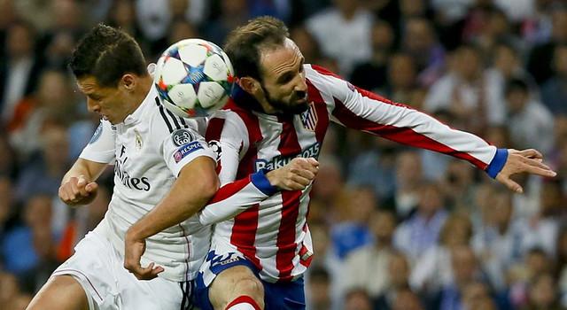 """El delantero mexicano del Real Madrid Javier Hernández """"Chicharito"""" salta por el balón con Juanfran, del Atlético de Madrid"""