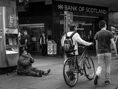 Bank of Scotland (Leanne Boulton) Tags: monochrome urban street candid streetphotography candidstreetphotography streetlife sociallandscape socialdocumentary woman female face facial expression eyecontact candideyecontact eyes hands prayer beggar begging homeless gang poverty cash bank money finance wealth juxtaposition tone texture detail depth natural outdoor light shade shadow city scene human life living humanity people society culture canon 7d wideangle black white blackwhite bw mono blackandwhite glasgow scotland uk