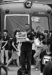Proposal (ontheheath) Tags: tokyo japan shibuya scramble man marriage proposal sign flower crowd summer city street