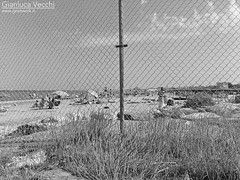 Seaside (Gianluca Vecchi Photography) Tags: blackandwhite bnw bw monochrome outdoor day daylight sea seaside beach fence chainlinkfence italy emiliaromagna cervia people pole post grass sand summer