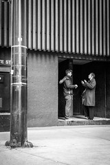 A quick, cold chat (dharder9475) Tags: blackandwhite bw woman man building candid strangers streetphotography conversation 2015 privpublic
