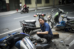 Scooter Mechanic (banpreso) Tags: china street new broken up work 35mm canon fix shanghai crash wheels fast scooter move dirty tires tired oil f2 wreck job mechanic wrench exhaust fd