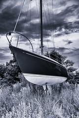 Blue-Sailboat-.On-Land (AroundMyTown) Tags: sailboat sailboatonland clouds disuse foreboding neglect abandonment decay