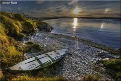 North Voe Whalsay, Shetland (Ivan Reid) Tags: sundog sunrise sunset sun calm blue sky boat fourereen beach stones pebles summer shetland whalsay rainbow reflection rowing