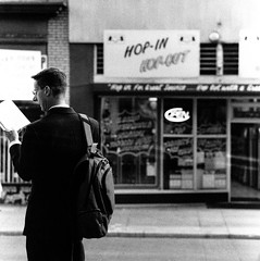 (christait) Tags: street blackandwhite bw canada man calgary reading hasselblad suit alberta backpack commuter yyc ilforddelta3200 500cm 7ave hopinhopout rodinal1100stand2hrs
