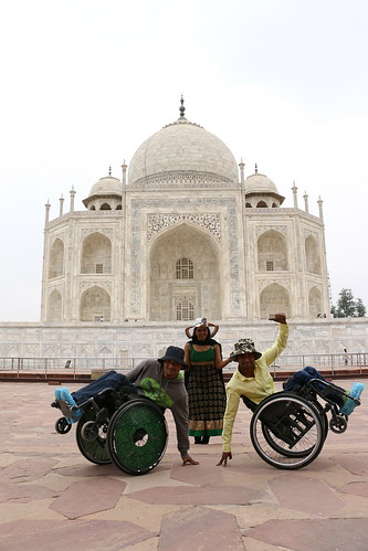 Accessible Tour of Taj Mahal:The travellers happily posing in their wheelchairs with the beautiful Taj as the backdrop.