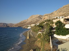 quiet mesouri beach (squeezemonkey) Tags: kalymnos greece mesouri beach mesouribeach landscape sea coast shore mountains rock village sunbeds