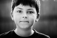 My Son (Greig Reid) Tags: portrait blackandwhite bw monochrome face outside outdoors eyes dof sam availablelight grain naturallight son depthoffield backlit headandshoulders landscapeformat