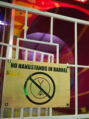 Handstands in Barrel (bburky) Tags: carnival sign yellow warning fence gate ride statefair barrel fair handstand railing