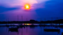 Sunrise, pushing through very thick clouds... (tomk630) Tags: virginia potomac sunrise clouds nature boats usa