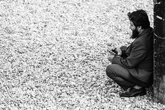 Beach Suit (sawyersource) Tags: street uk people blackandwhite bw white man black beach monochrome socks beard person photography prime seaside nikon shoes brighton sitting phone dress bright britain no candid united sigma style kingdom pebbles clothes business suit gb sat knees leaning dressed crouch 105mm d7200