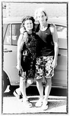 Day 216, 2016, a photo a day. (lizzieisdizzy) Tags: monochrome blackandwhite portrait outside outdoors bright sunny daytime people two couple male female married smiling happy car carpark summer warmweather tshirt vest shorts patterned flowery summerdress pretty shorthair relaxed
