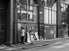 Northern Quarter #100 (Peter.Bartlett) Tags: manchester niksilverefex woman wall window unitedkingdom urbanarte people urban facade olympuspenf noiretblanc streetphotography standing cigarette peterbartlett lunaphoto man girl shutter candid uk m43 couple monochrome bw gate sign blackandwhite microfourthirds city