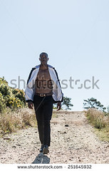 stock-photo-african-black-male-model-wearing-black-suit-with-white-unbuttoned-shirt-walking-down-gravel-path-251645932 (Soft Focus Photography) Tags: road white mountain man black sexy male men fashion businessman shirt modern standing dark walking person model open looking adult body path walk african background coat young formal handsome style professional business suit pack tuxedo american topless attractive elegant six toned success isolated unbuttoned gravel confident stylish
