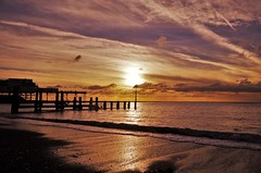 reflected glory (Sundornvic) Tags: aberystwyth wales beach sea sky sun sunset clouds blue white glow pier jetty waves ripples rocks