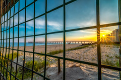 Sunburst Through The Fence (Stuart Schaefer Photography) Tags: sunburst fence sonya7m2 sand cloudscape sunset landscape condos water navarrebeach outdoors outdoor pier seascape clouds florida