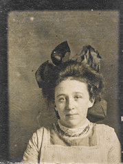Photo booth portrait of a young woman with a large bow (simpleinsomnia) Tags: old woman white black girl monochrome sepia vintage booth found photo blackwhite pretty photobooth antique snapshot photograph bow vernacular foundphotograph