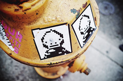 8-bit (Eric Flexyourhead (shoulder injury, slow)) Tags: seattle wa washington usa capitolhill 12thavenue city urban detail fragment street streetfragment hydrant firehydrant yellow art graffiti sticker streetart 8bit vignette shallowdepthoffield bokeh ricohgr