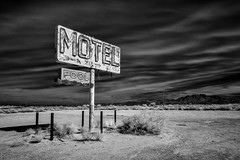 route 66 infrared. yucca, az. 2014. (eyetwist) Tags: eyetwistkevinballuff eyetwist route66 arizona yucca motel neon sign pool abandoned mojavedesert mojave desert derelict dirt barren bleak lonely nikon nikond7000 d7000 nikkor capturenx2 1024mmf3545g nik silver efex silverefexpro ir infrared digital bw blackwhite black white monochrome blacksky contrast longexposure filter 093 schneider bw093 type typography typographic arrow clouds roadsideamerica americana landscape highdesert desertscape windswept forgotten bypassed american west wideangle route 66 motherroad roadtrip landmark interstate 40 i40