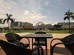 brief respite (DOLCEVITALUX) Tags: plaza park canonpowershotsx50hs outdoor coffeebar cafe chairs tree sky skies bluebay bluebaymanila