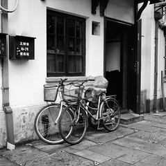 Alley in Hangzhou (8) - Together (Purple Field) Tags: china street bw 120 6x6 tlr film monochrome bicycle analog rolleiflex zeiss walking square t alley iso400 delta 400 carl hangzhou medium 中国 散歩 ilford 二眼レフ 杭州 zhejiang 自転車 路地 f35 75mm モノクロ 白黒 tessar 銀塩 ストリート フィルム デルタ 浙江省 正方形 アナログ ローライフレックス 中判 canoscan8800f テッサー stphotographia イルフォード カール・ツァイス
