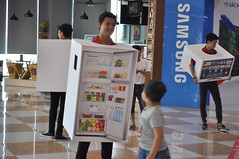 Cool character (Roving I) Tags: homeappliances vicomcentre promotions sales retail fridges refrigerators smiles boxes cartons boys samsung malls shopping danang vietnam models