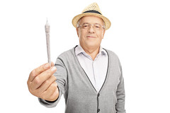 Cheerful mature man holding medicinal marijuana (kushtourism) Tags: 60s adult background blunt cancer cannabis cap caucasian cheerful cigarette doobie drug elderly expression ganja giving glasses glaucoma grass handing happy hat illegal isolated joint legal lifestyle looking male man marijuana mature medical medicinalmarijuana modern narcotic offering old one person pose posing pot senior single smile smiling studio weed white