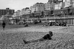 Staring at the Sun (James Hodgson Photography) Tags: beach girl woman black white pebble gin gt stare bathe lay relax listen headphones brighton kemp town