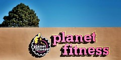 Thumbs Up At Planet Fitness (Cooling Down Again Yay!!!) Tags: odc thumbsup planetfitness letters purple hand thumb tree roof stucco sky blue beige buildiong green
