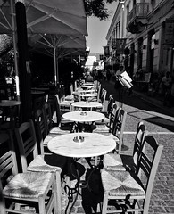 Monasteraki charm (Mad Mou) Tags: afternoon sunlight summer blackandwhite contrast pedestrian umbrella chairs tables neighborhood athens monasteraki caf greece