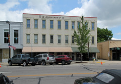 Longnecker Building  Eaton, Ohio (Pythaglio) Tags: county street blue trees windows ohio sky building brick cars clouds altered awning painted flag 11 structure historic sidewalk american eaton lettering storefronts automobiles preble awnings remodeled 1867 threestory longnecker pre428