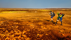 The Tourists (departing(YYZ)) Tags: africa camera travel red people orange male men yellow rock landscape outside japanese extreme rocky tourist exotic heat daytime ethiopia sulfur volcanic twopeople active vulcanism otherworldly extremeenvironment danakildepression sonnartfe55mmf18zalens