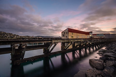 Shelly Bay I (buddythunder) Tags: old morning pink newzealand reflection broken clouds dawn rocks purple shed perspective peaceful wideangle calm wharf wellington distressed leaning sheds shabby wharves shellybay blemished