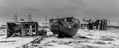 that was some party .......... (frattonparker) Tags: nikond600 tamron28300mm raw lightroom6 monochrome panorama dungeness abandoned derelict deserted boatwreck hut hull hulk sheds railway pylons shingle nets frattonparker btonner